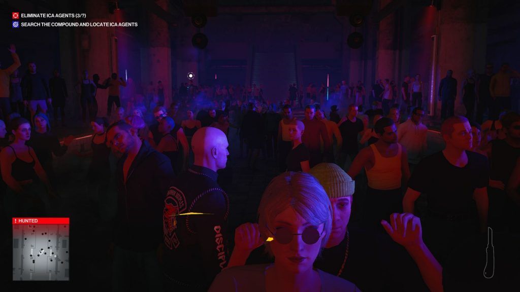 A screenshot of Agent 47 in the middle of a crowded dance floor in a club
