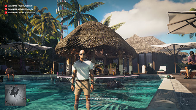 Ian Hitman stands in a pool in front of a swanky pool bar. He's wearing shorts and a white shirt, and looks like he might be on a normal holiday, almost.