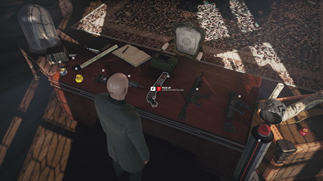 A screenshot of Hitman 3's interactive Dartmoor benchmark, showing Agent 47 standing in front of table full of weapons in an old study.