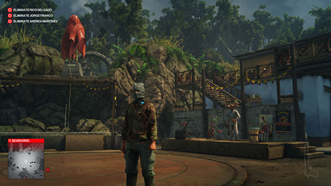 Ian Hitman in the Santa Fortuna level of Hitman 2. He is wearing camouflage combats and a balaclava, and is in a small town square in front of a stage, surrounded by jungle plants.