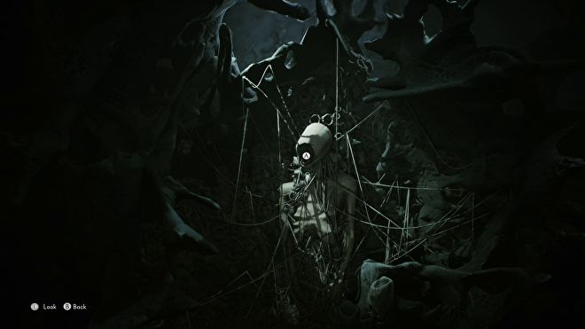 Mariane is looking at a trapped spirit in the world of the dead. It is an emaciated, faceless body held to a wall by many looping strings