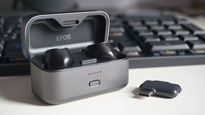 A photo of the EPOS GTW 270 Hybrid wireless earbuds inside their charging case, next to their USB-C adaptor