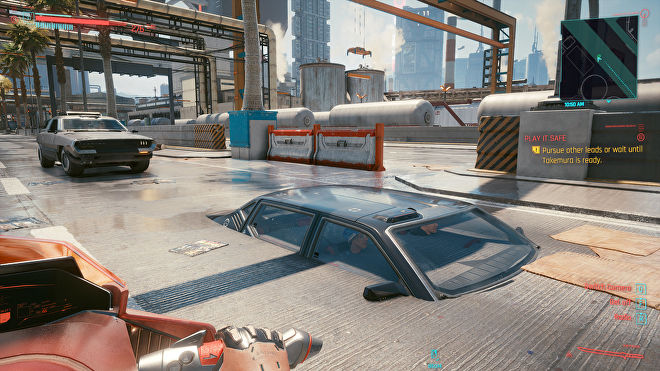 Two people sat in a car which has sunk deep into the road in a Cyberpunk 2077 screenshot.