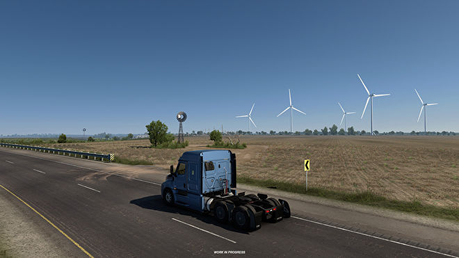 American Truck Simulator Texas - A truck cab drives down a two lane road with fields and wind turbines in the background.