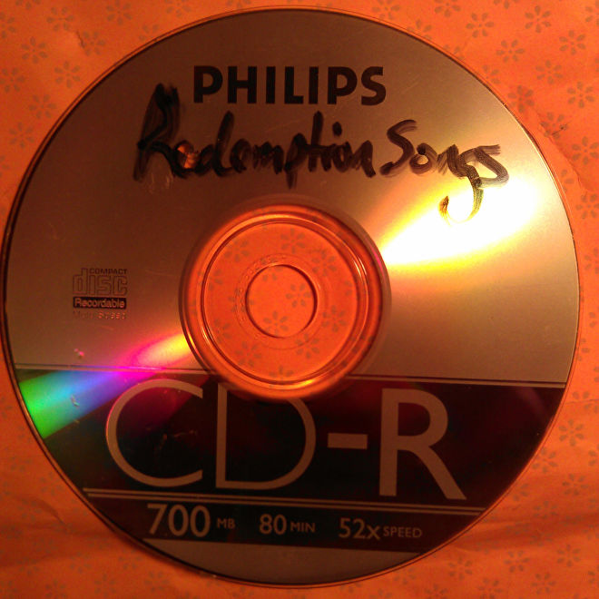 A photograph of a CD-R with the handwritten label 'Redemption Songs'.
